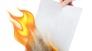 Image of hand holding burning paper